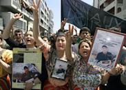 The mother (R) and sister (2nd R) of Massinissa Guermah hold pictures of him during a demonstration in April 2002, a year after he was killed by police