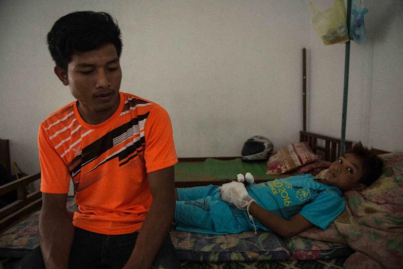 13-year-old Viet (R) lies on a hospital bed alongside his brother in Xieng Khoang, Laos on June 3, 2016 after losing several fingers to an unexploded bomblet (AFP Photo/Alison McCauley)