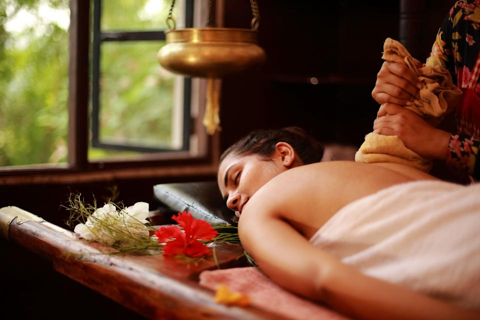 Female therapist treating a young lady in an ayurvedic spa following Indian traditional method.