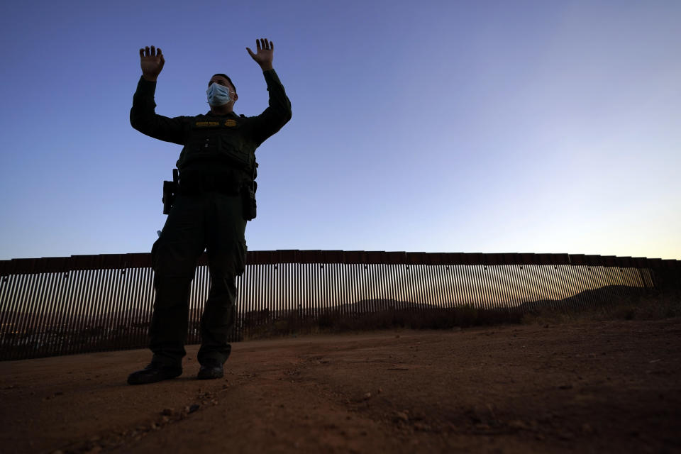 Border Patrol agent Justin Castrejon gestures as he describes the difficulties of climbing the new section of the border structure, behind, Thursday, Sept. 24, 2020, near Tecate, Calif. President Donald Trump's reshaping of U.S. immigration policy may be most felt in his undoing of asylum. Castrejon says migrants pay $8,000 to $10,000 to be guided through the mountains and picked up by a driver once they reach a road. (AP Photo/Gregory Bull)