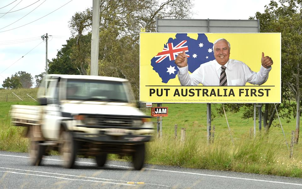 Photo taken on May 3, 2019 shows a ute driving past an election sign for mining magnate Clive Palmer's United Australia Party in Bowen in northern Queensland. - In conservative-leaning Queensland state, disillusioned voters are moving further right to support the anti-immigration One Nation Party and Clive Palmer's United Australia Party ahead of the election on May 18, 2019 (Photo by PETER PARKS / AFP) / TO GO WITH: Australia-politics-vote, FOCUS by Glenda KWEK        (Photo credit should read PETER PARKS/AFP via Getty Images)