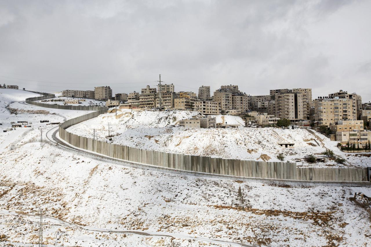 Heavy snowfall is seen around a section of the controversial Israeli barrier in Shuafat refugee camp in the West Bank near Jerusalem December 13, 2013. A snowstorm of rare intensity blanketed the Jerusalem area and parts of the occupied West Bank on Friday, choking off the city and stranding hundreds in vehicles on impassable roads. REUTERS/Baz Ratner (WEST BANK - Tags: ENVIRONMENT)
