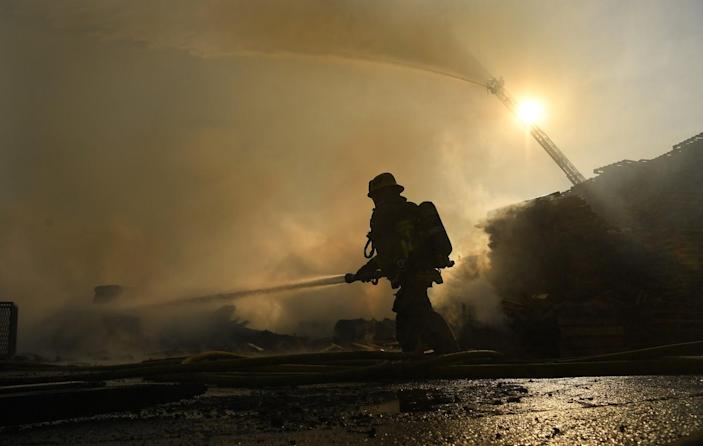 A firefighter sprays water as a fire engine in the background does the same