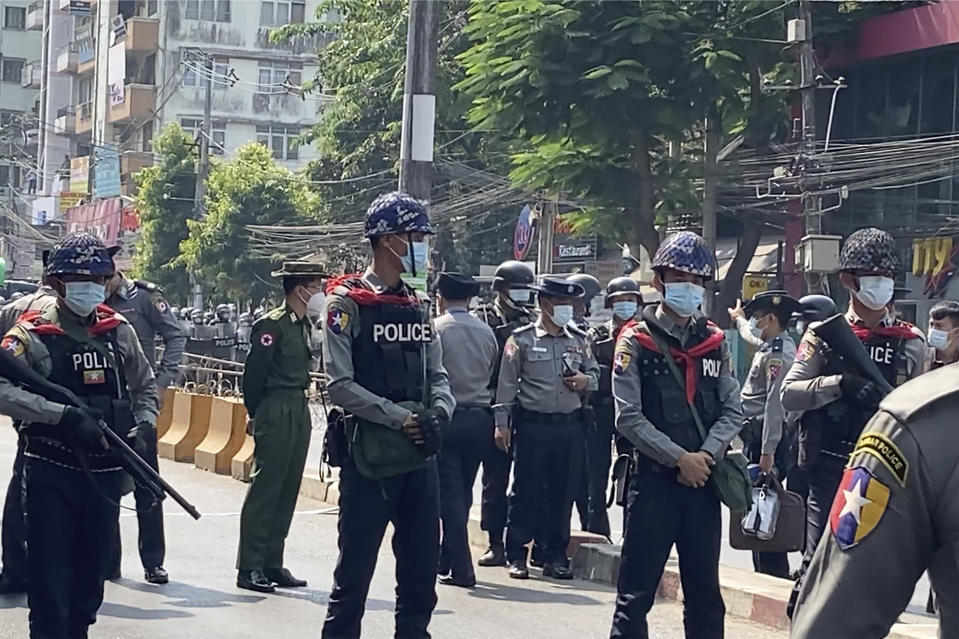 In this image made from video, Myanmar police block the road to prevent protesters from marching forward Saturday, Feb. 6, 2021 in Yangon, Myanmar. The military authorities in charge of Myanmar broadened a ban on social media following this week's coup, shutting access to Twitter and Instagram, while street protests continued to expand Saturday as people gathered again to show their opposition to the army takeover. (AP Photo)