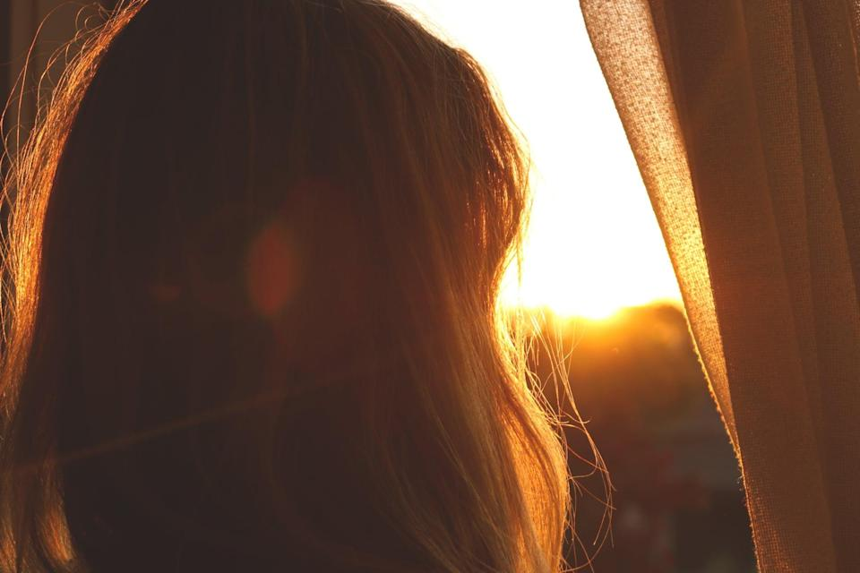 Woman at sunset looking out window