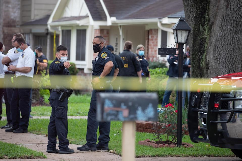 Police officials stand outside a home in southwest Houston on April 30, 2021. / Credit: ADREES LATIF / REUTERS