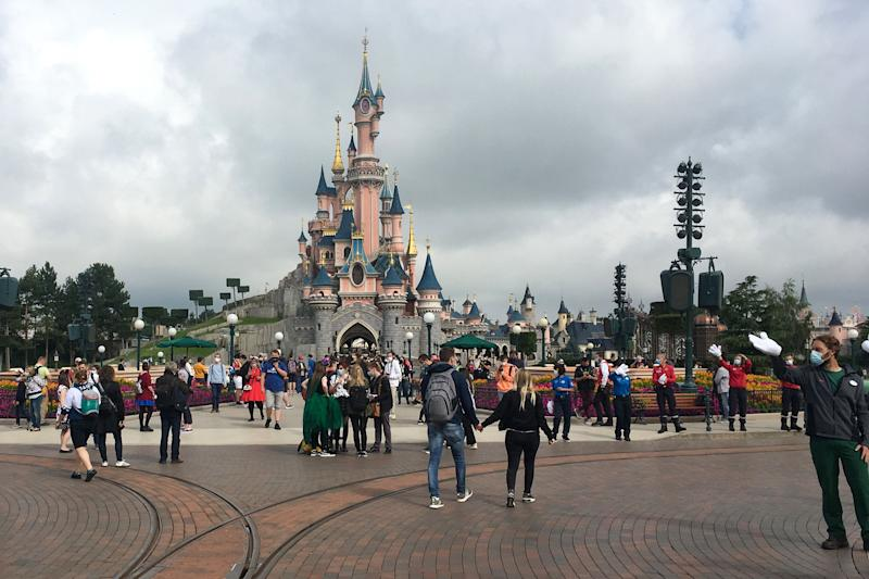 Visitors and staff wearing protective face masks, walk down the Main Street of Disneyland Paris in Marne-la-Vallee, near Paris, on July 15, 2020, as Disneyland Paris begins phased reopening after months-closure aimed at stemming the spread of the novel coronavirus (COVID-19). (Photo by Aurelia MOUSSLY / AFP) (Photo by AURELIA MOUSSLY/AFP via Getty Images)