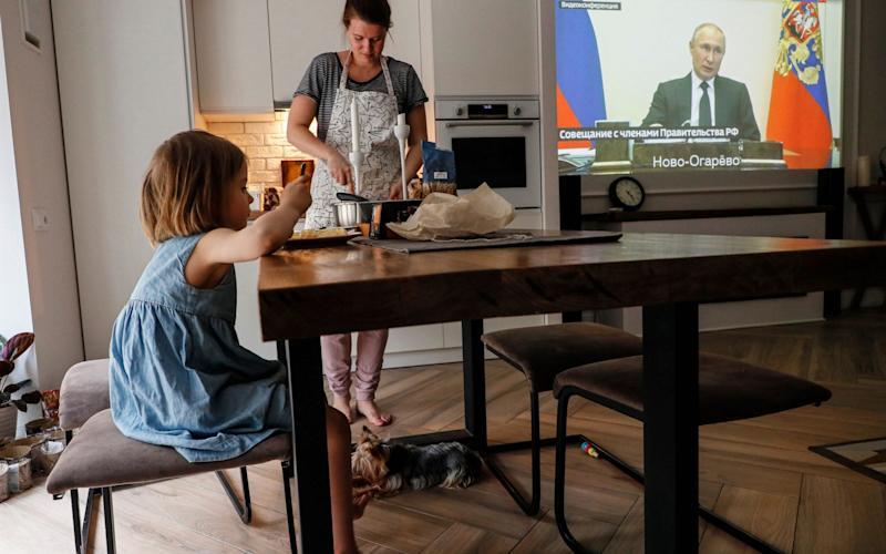A family watches Mr Putin on a television screen - SERGEI ILNITSKY/EPA-EFE/Shutterstock