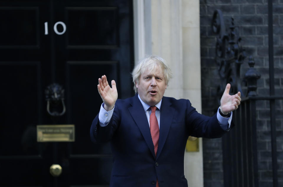 """Britain's Prime Minister Boris Johnson applauds on the doorstep of 10 Downing Street in London during the weekly """"Clap for our Carers"""" Thursday, May 28, 2020. The COVID-19 coronavirus pandemic has prompted a public display of appreciation for care workers. The applause takes place across Britain every Thursday at 8pm local time to show appreciation for healthcare workers, emergency services, armed services, delivery drivers, shop workers, teachers, waste collectors, manufacturers, postal workers, cleaners, vets, engineers and all those helping people with coronavirus and keeping the country functioning while most people stay at home in the lockdown. (AP Photo/Kirsty Wigglesworth)"""