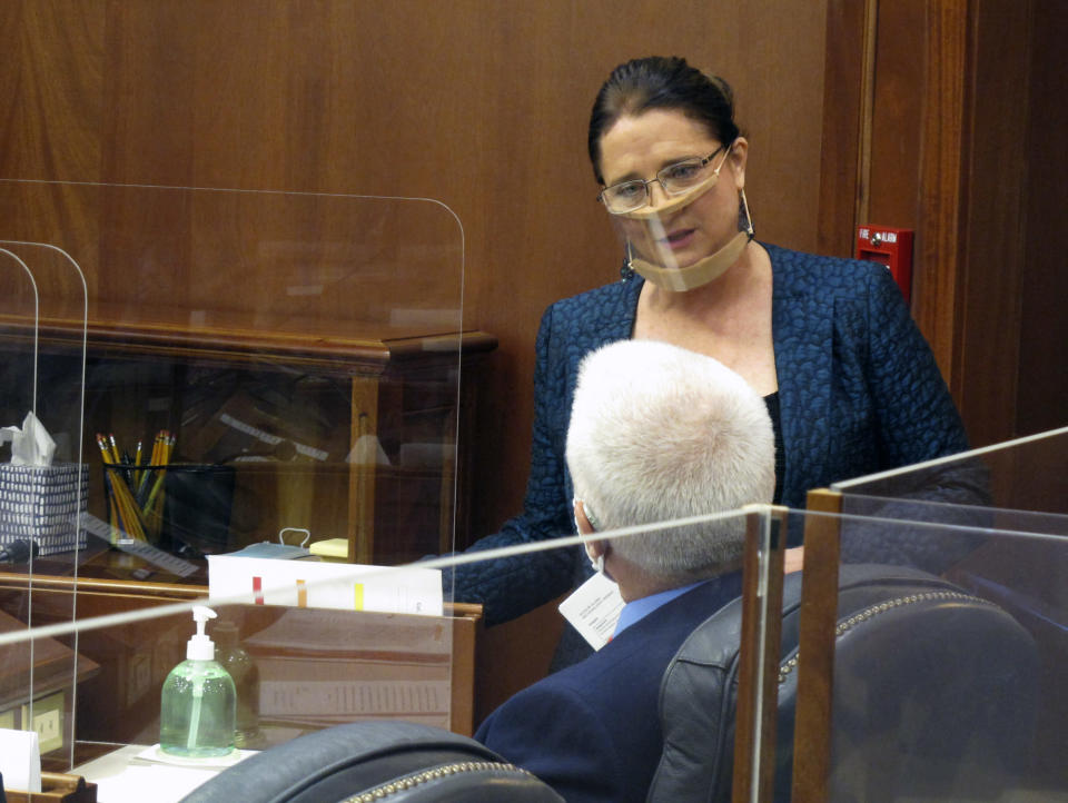 """Alaska state Sen. Lora Reinbold speaks to Sen. Roger Holland before the start of the Senate floor session on Monday, April 26, 2021, in Juneau, Alaska. Reinbold said she traveled to Juneau by vehicle and ferry when Alaska Airlines said she was not permitted to fly on the carrier for what the airline said was her """"continued refusal to comply with employee instruction regarding the current mask policy."""" It was not clear how long the suspension would be in place. (AP Photo/Becky Bohrer,Pool)"""