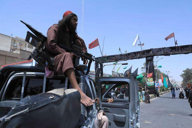 A Taliban fighter stands guard atop a vehicle near the site of an Ashura procession which is held to mark the death of Imam Hussein, the grandson of Prophet Mohammad, along a road in Herat on August 19, 2021, amid the Taliban's military takeover of Afghanistan. (Photo by AREF KARIMI / AFP) (Photo by AREF KARIMI/AFP via Getty Images) (Photo: AREF KARIMI via Getty Images)