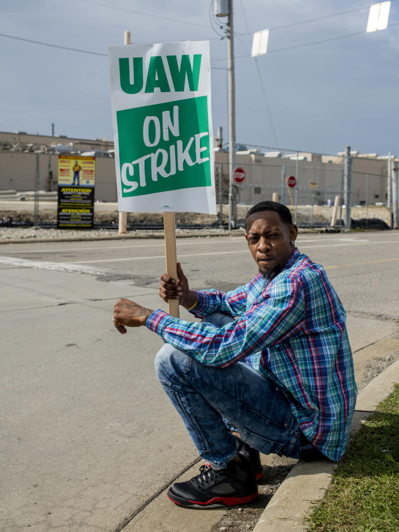 Rory Lee of Flint, Mich., sits on the curb as he protests alongside other General Motors employees outside of the Flint Assembly Plant on Sunday, Sept. 15, 2019 in Flint. GM autoworkers officially go on strike at midnight Sunday after UAW leadership voted to do so Sunday morning.  (Jake May/The Flint Journal via AP)