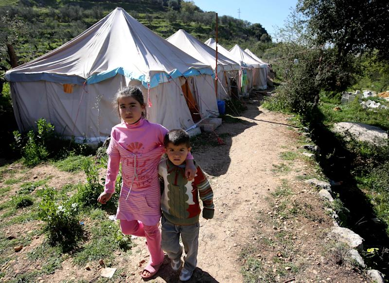 FILE - In this March 14, 2013 file photo, Syrian refugees walk next of their tents at a small refugee camp, in Ketermaya village, southeast of Beirut, Lebanon. A housing unit designed for the United Nations' refugee agency to offer shelter for those, fleeing conflict has become the latest source of friction between Lebanese politicians and aid organizations trying to manage the massive number of Syrian refugees in the country. Lebanon's refusal to set up any kind of organized accommodation for tens of thousands of Syrians, including refugee camps. (AP Photo/Hussein Malla, File)