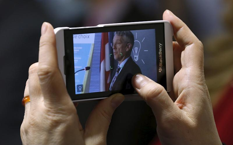 A journalist uses a smartphone to record CRTC Chairman Blais as he speaks during a news conference in Gatineau