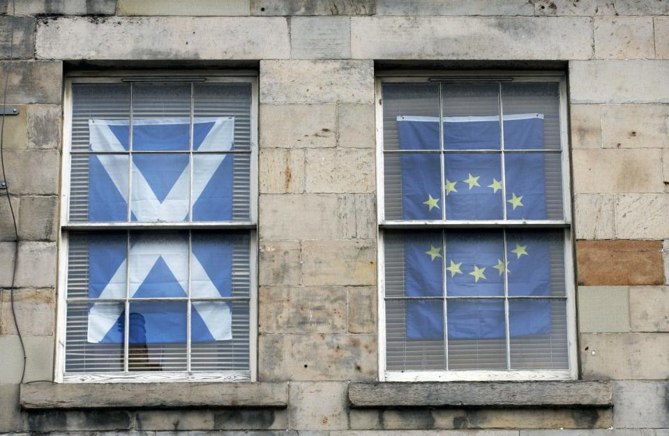 """<span class=""""caption"""">A Scottish Saltire flag hangs in the window of an apartment in Edinburgh, Scotland, next to the EU flag in August 2020. Scotland could vote to separate from the U.K. in 2021.</span> <span class=""""attribution""""><span class=""""source"""">(AP Photo/David Cheskin)</span></span>"""