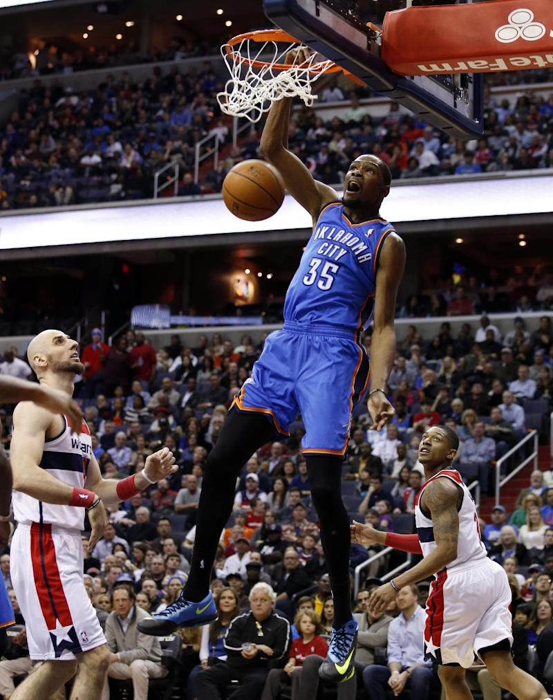 Oklahoma City Thunder forward Kevin Durant (35) dunks as Washington Wizards center Marcin Gortat, left, from Poland, and guard Bradley Beal, right, watch in the first half of an NBA basketball game on Saturday, Feb. 1, 2014, in Washington. (AP Photo/Alex Brandon)