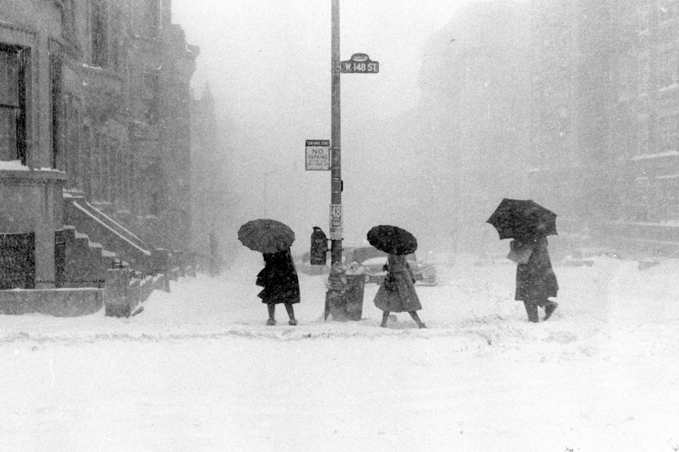 Three pedestrians with umbrellas struggle against snow and wind as they cross an intersection at 148th Street in Harlem. The nor'easter of February 1961 reached blizzard proportions in New York, with some areas receiving up to 20 inches of snow.