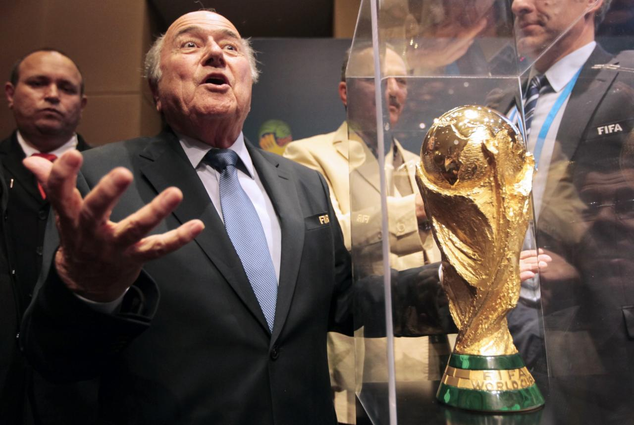 FIFA President Sepp Blatter gestures next to the World Cup trophy after a media conference in Sao Paulo June 5, 2014. The 2014 World Cup will be held in 12 cities in Brazil from June 12 to July 13. REUTERS/Paulo Whitaker (BRAZIL - Tags: SPORT SOCCER WORLD CUP TPX IMAGES OF THE DAY)