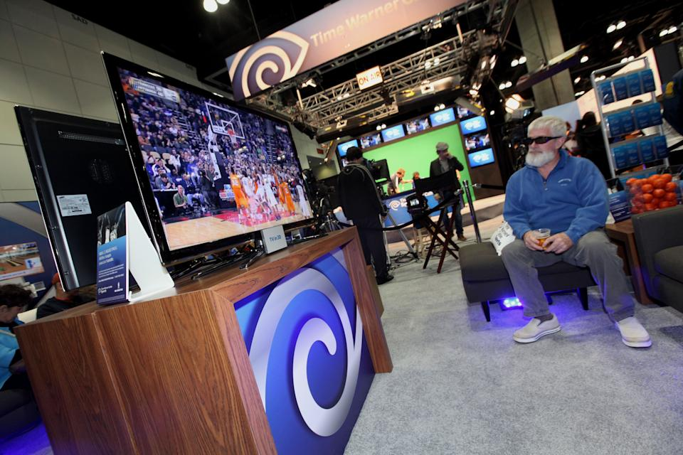 A consumer watches TV in 3D at the Time Warner Cable Sports Step Thru the Screen Interactive Booth at NBA Jam Session, in Los Angeles, on Thursday, Feb. 17, 2011. (Casey Rodgers / AP Images for Time Warner Cable Sports)