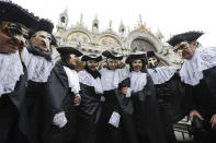 """FILE - In this Feb.11, 2017 file photo, men wears masks, some of them pest doctor masks, in St. Mark's Square in Venice, Italy. This carnival mask derives from 16th century doctors wearing beak-nosed masks filled with aromatic herbs to cleanse the air they breathed when treating the sick. Venice's central place in the history of battling pandemics and pestilence will come into focus at this year's Venice Film Festival, which opens Wednesday, Sept. 1, 2021, with the premiere of Pedro Almodovar's in-competition """"Madres Paralelas"""" (Parallel Mothers), which he developed during Spain's 2020 coronavirus lockdown, one of the harshest in the West. (AP Photo/Luca Bruno)"""