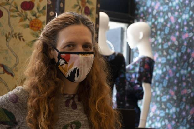 Katrin Leblond poses for portrait wearing one of her own mask designs at her store in Montreal. She used fabric from her textile collection to start making masks.  (Submitted by Madeleine Ellis - image credit)