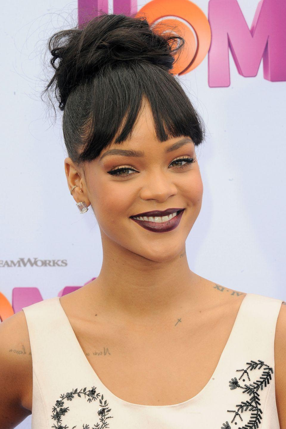 <p>Simple and chic, Rihanna wears a top knot at the center of her crown with bangs.</p>