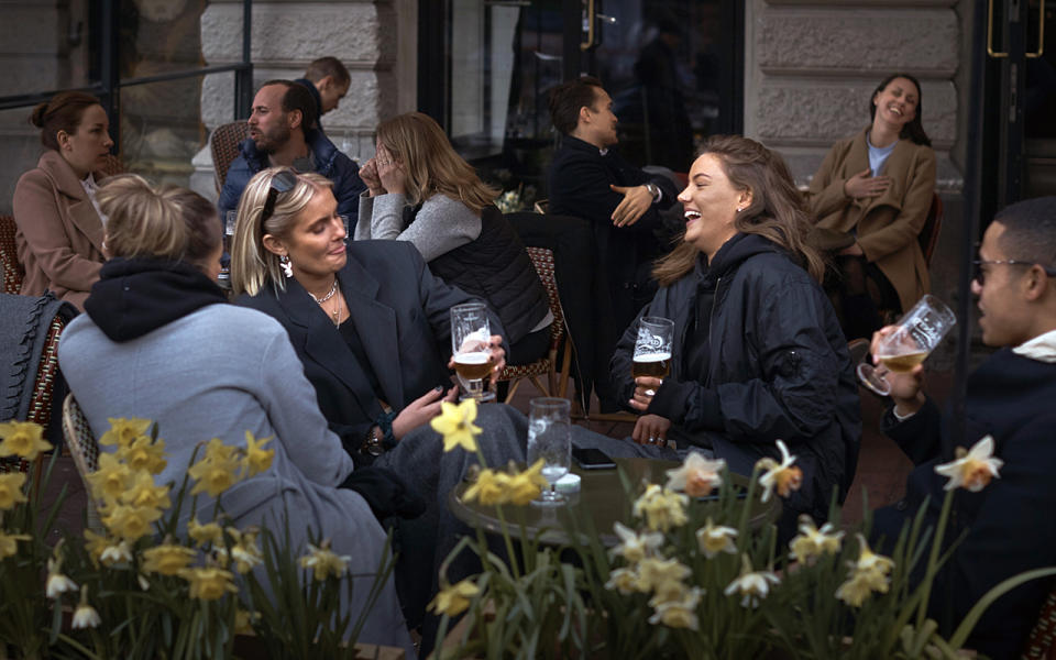 People chat and drink outside a bar in Stockholm, Sweden. Source: AP