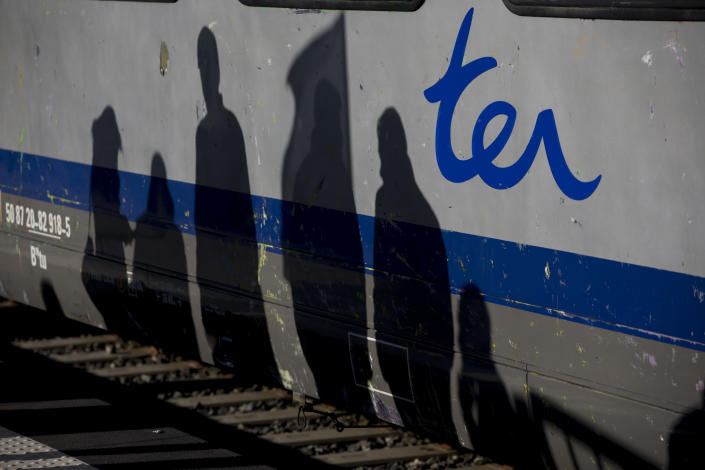 The shadows of railway workers are cast on a regional line train during a union general assembly meeting at the Gare St-Charles station in Marseille, southern France, Monday, Dec. 9, 2019. Paris commuters inched to work Monday through exceptional traffic jams, as strikes to preserve retirement rights halted trains and subways for a fifth straight day. (AP Photo/Daniel Cole)