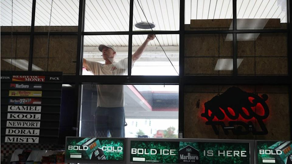 A man boards up a Louisiana store as the state braces itself for Hurricane Laura