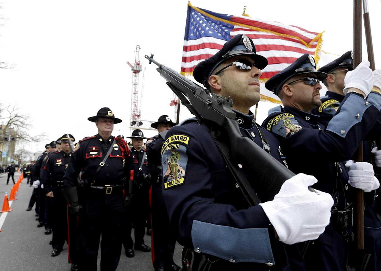 Members of a police honor guard, front, lead a column of law enforcement officials into a memorial service for fallen Massachusetts Institute of Technology police officer Sean Collier, in Cambridge, Mass., Wednesday, April 24, 2013. Collier was fatally shot on the MIT campus Thursday, April 18, 2013. Authorities allege that the Boston Marathon bombing suspects were responsible. (AP Photo/Steven Senne)