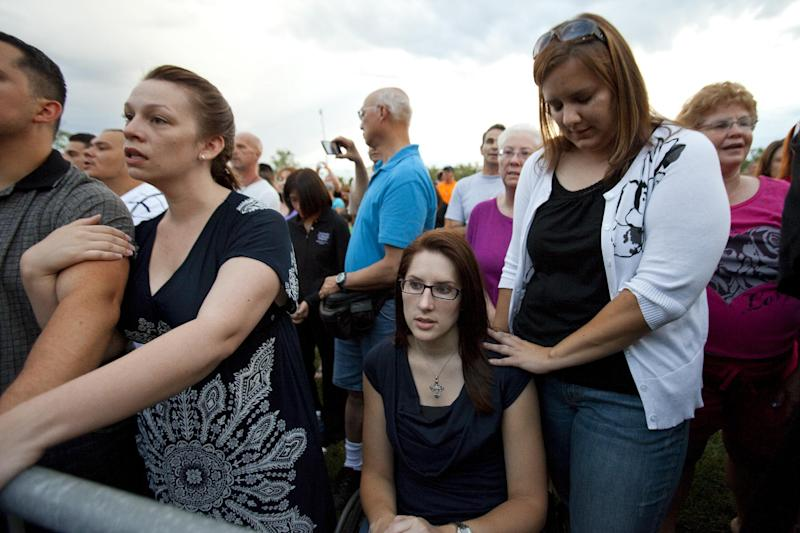 "Anne Marie Hochhalter, 30, bottom, and her friend Roxy Chesser, 30, second from right, attend a prayer vigil, held to remember the lost and injured in Friday's mass shooting at a movie theater, in a park outside the Aurora Municipal Center in Aurora, Colo., Sunday July 22, 2012. Hochhalter, a paralyzed victim of the Columbine High School tragedy over 12 years ago, and other survivors of the 1999 massacre reached out to people who survived the theater shooting. Twelve people were killed and dozens were injured in a shooting attack during a showing of the Batman movie, ""The Dark Knight Rises."" Police have identified the suspected shooter as James Holmes. (AP Photo/Barry Gutierrez)"
