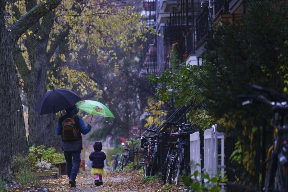 """<span class=""""caption"""">Montréal father Dominic Desilets walks his daughter Benedicte to daycare on a rainy morning on Oct. 26, 2020. </span> <span class=""""attribution""""><span class=""""source"""">(THE CANADIAN PRESS/Paul Chiasson)</span></span>"""