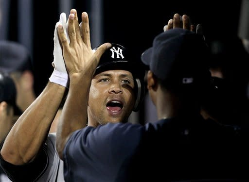 New York Yankees' Alex Rodriguez, left, gets a high-five from teammate Ivan Nova after hitting a grand slam in the eighth inning of a baseball game against the Atlanta Braves on Tuesday, June 12, 2012, in Atlanta. (AP Photo/David Goldman)