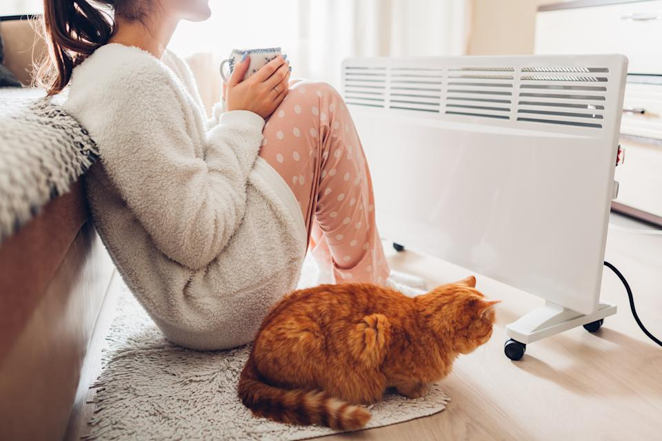 Woman warming and drinking tea with cat sitting by device and wearing warm clothes.