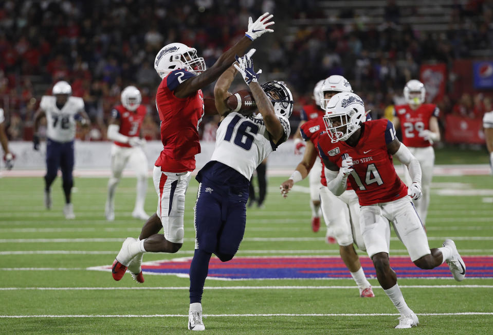 Utah State wide receiver Jordan Nathan catches a pass over his shoulder to set up a touchdown as Fresno State defensive backs Chris Gaston, left, and Jaron Bryant defend during the first half of an NCAA college football game in Fresno, Calif., Saturday, Nov. 9, 2019. (AP Photo/Gary Kazanjian)
