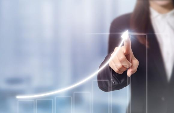 A person pointing to an upwardly sloping arrow above a rising bar chart