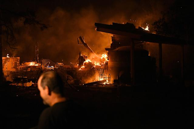 <p>Scott Whitley watches as the Ponderosa fire burns a garage at his residence east of Oroville, Calif., Aug. 29, 2017. (Photo: Noah Berger/Reuters) </p>