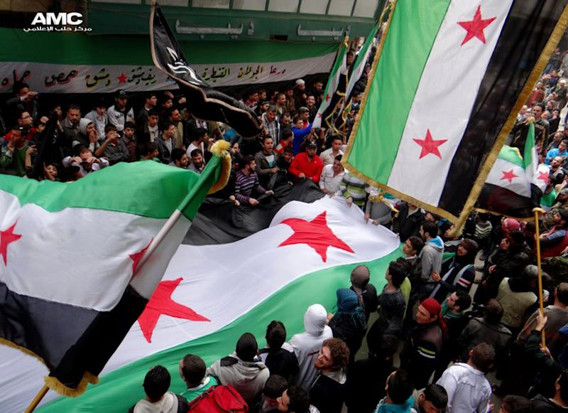 "In this citizen journalism image provided by Aleppo Media Center AMC which has been authenticated based on its contents and other AP reporting, anti-Syrian regime protesters, wave the Syrian revolutionary flags during a protest to mark the second anniversary of the their uprising, in Aleppo, Syria, Friday March 15, 2013. The chief of Syria's main, western-backed rebel group marked the second anniversary of the start of the uprising against President Bashar Assad on Friday by pledging to fight until the ""criminal"" regime is gone. (AP Photo/Aleppo Media Center, AMC)"