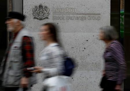 FILE PHOTO: People walk past the entrance of the London Stock Exchange in London