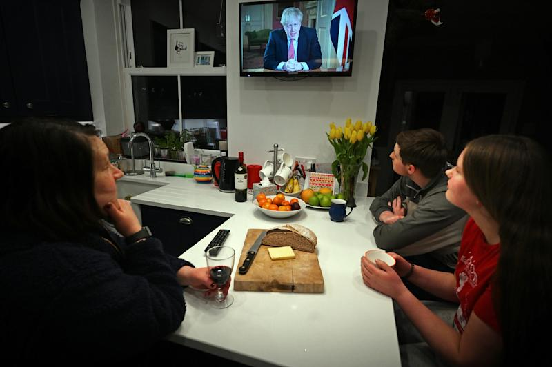 "Members of a family listen as Britain's Prime Minister Boris Johnson makes a televised address to the nation from inside 10 Downing Street in London, with the latest instructions to stay at home to help contain the Covid-19 pandemic, from a house in Liverpool, north west England on March 23, 2020. - Britain on Monday ordered a three-week lockdown to tackle the spread of coronavirus, shutting ""non-essential"" shops and services, and banning gatherings of more than two people. ""Stay at home,"" Prime Minister Boris Johnson said in a televised address to the nation, as he unveiled unprecedented peacetime measures after the death toll climbed to 335. (Photo by Paul ELLIS / AFP) (Photo by PAUL ELLIS/AFP via Getty Images)"
