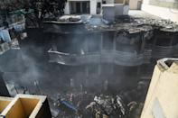 Rescue workers search for victims at the site after a Pakistan International Airlines aircraft crashed at a residential area in Karachi on May 22, 2020. - A Pakistani passenger plane with nearly 100 people on board crashed into a residential area of the southern city of Karachi on May 22. (Photo by Asif HASSAN / AFP) (Photo by ASIF HASSAN/AFP via Getty Images)