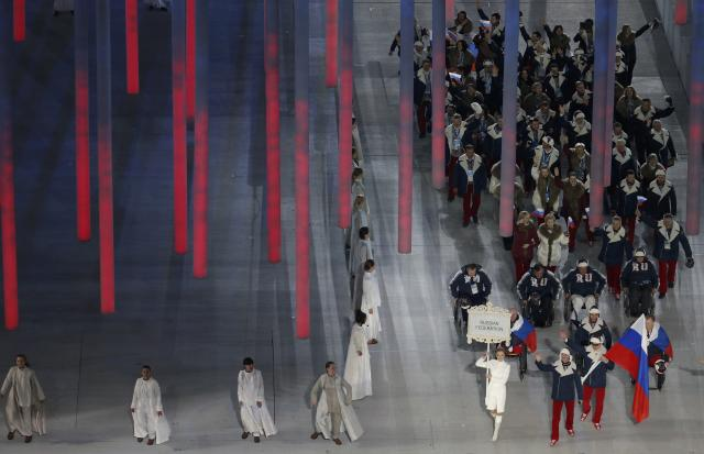 Russia's flag-bearer Valerii Redkozubov (R), leads his country's contingent during the opening ceremony of the 2014 Paralympic Winter Games in Sochi March 7, 2014. REUTERS/Christian Hartmann (RUSSIA - Tags: SPORT OLYMPICS)