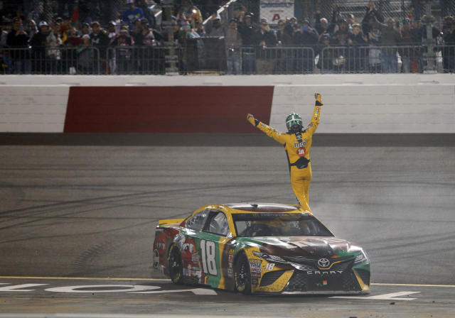 "<a class=""link rapid-noclick-resp"" href=""/nascar/sprint/drivers/947/"" data-ylk=""slk:Kyle Busch"">Kyle Busch</a> waves to the fans as he celebrates winning the NASCAR Cup Series auto race at Richmond Raceway in Richmond, Va., Saturday, April 21, 2018. (AP Photo/Steve Helber)"
