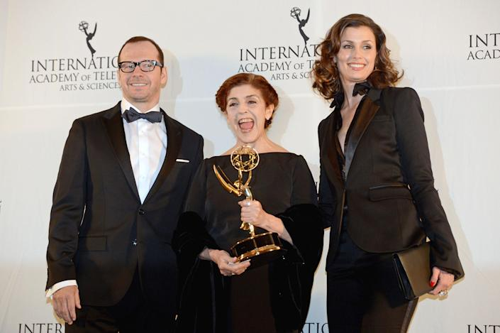 """Argentine actress Cristina Banegas, center, poses with presenters Donnie Wahlberg, left, and Bridget Moynihan after winning the Best Performance by an Actress award for her role in the miniseries """"Television por la Inclusion,"""" at the 40th International Emmy Awards, Monday, Nov. 19, 2012 in New York. (AP Photo/Henny Ray Abrams)"""