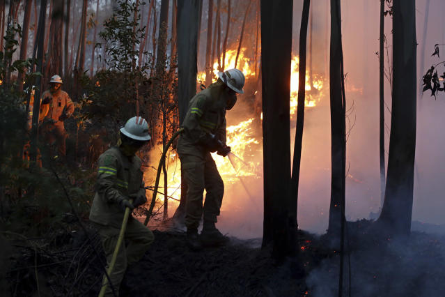 <p>Firefighters of the Portuguese National Republican Guard work to stop a forest fire from reaching the village of Avelar, central Portugal, at sunrise Sunday, June 18 2017. (Armando Franca/AP), </p>