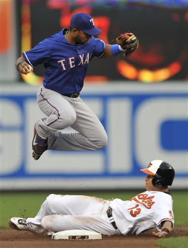 Baltimore Orioles' Manny Machado, bottom. is out at second as Texas Rangers shortstop Elvis Andrus jumps over him on a fielder's choice hit into by Nick Markakis in the first inning of a baseball game on Wednesday, July 10, 2013, in Baltimore. (AP Photo/Gail Burton)