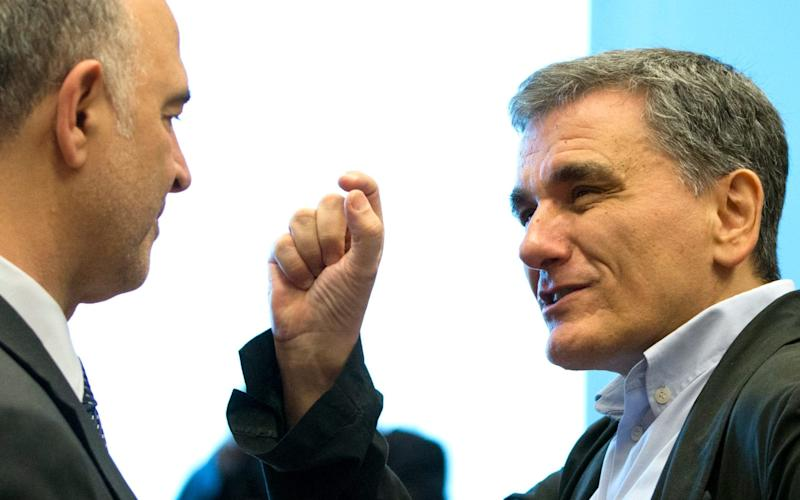 Greek Finance Minister Euclid Tsakalotos, right, speaks with European Commissioner for Economic and Financial Affairs Pierre Moscovici during a meeting of eurogroup finance ministers - AP