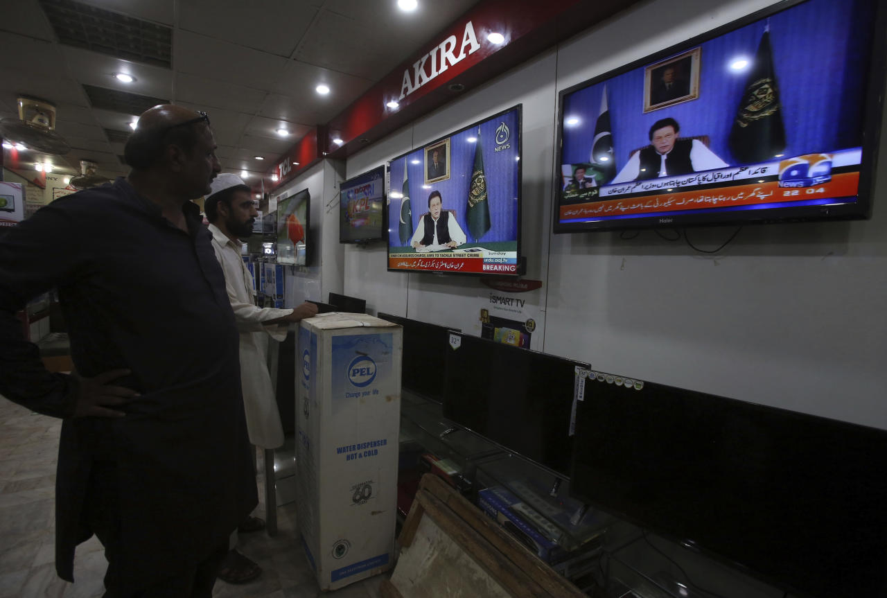 People watch a televised address by Pakistan's newly elected Prime Minister Imran Khan at an electronic shop in Karachi, Pakistan, Sunday, Aug. 19, 2018. Pakistan's newly elected prime minister Imran Khan Sunday said the country was in its worst economic condition and pledged to improve it by adopting austerity to cut government expenditure, introducing progressive taxation, end corruption and bringing back from abroad the plundered public money. (AP Photo/Fareed Khan)