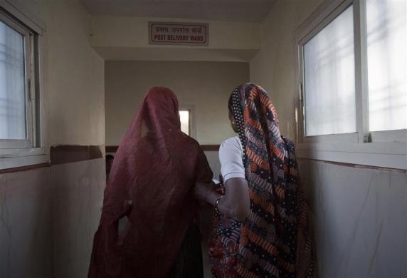 Anguri, a 26-year-old pregnant woman who just gave birth, is led to the post-delivery ward by a relative after she gave birth to a baby at a community health centre in the remote village of Chharchh, in the central Indian state of Madhya Pradesh, February 24, 2012.