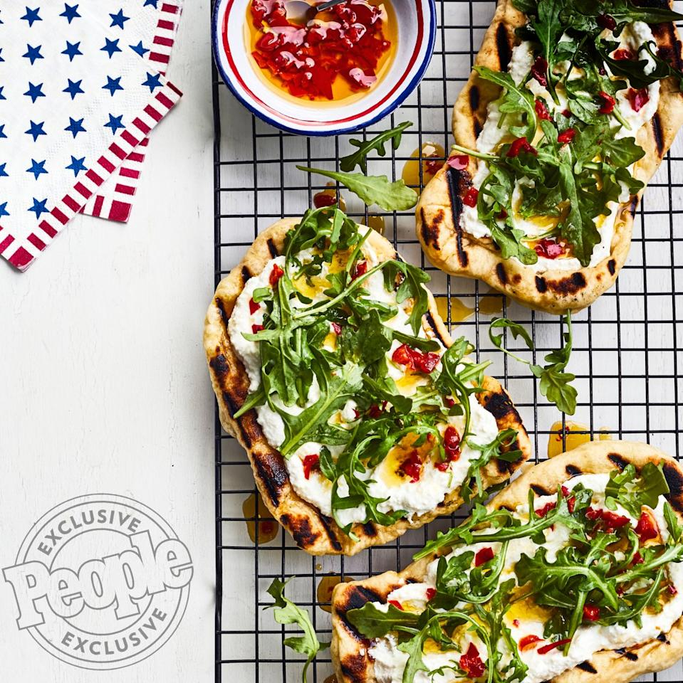"""Fresh store-bought dough makes these pies from Anne Burrell super easy to pull together. Cook them straight on the grill grates, then top with cheese, greens and a spicy chile oil.  Get the recipe <a href=""""https://people.com/food/anne-burrell-grilled-pizzas-with-ricotta-arugula-chile-oil-recipe/"""">HERE</a>."""